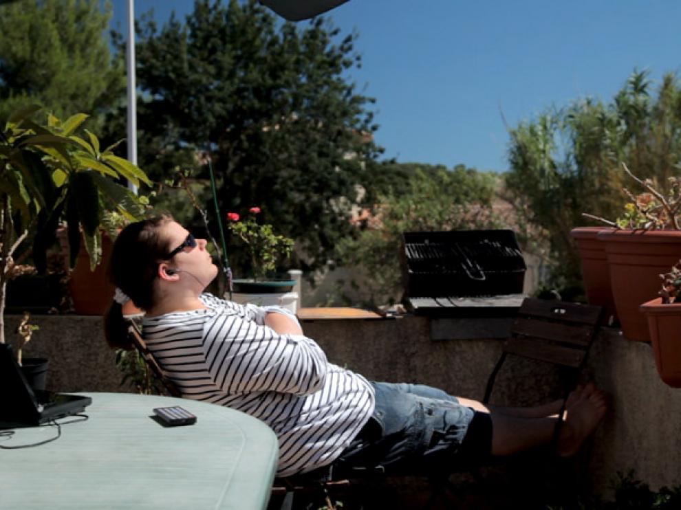 Armand, prenant le soleil, assis sur une terrasse