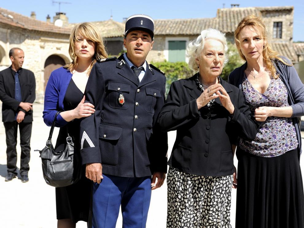 Trois femmes et un gendarme sont debout devant une grande bâtisse, ils regardent dans la même direction