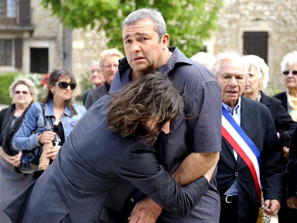 Un homme saute dans les bras d'un homme assez costaud, devant le regard des villageois