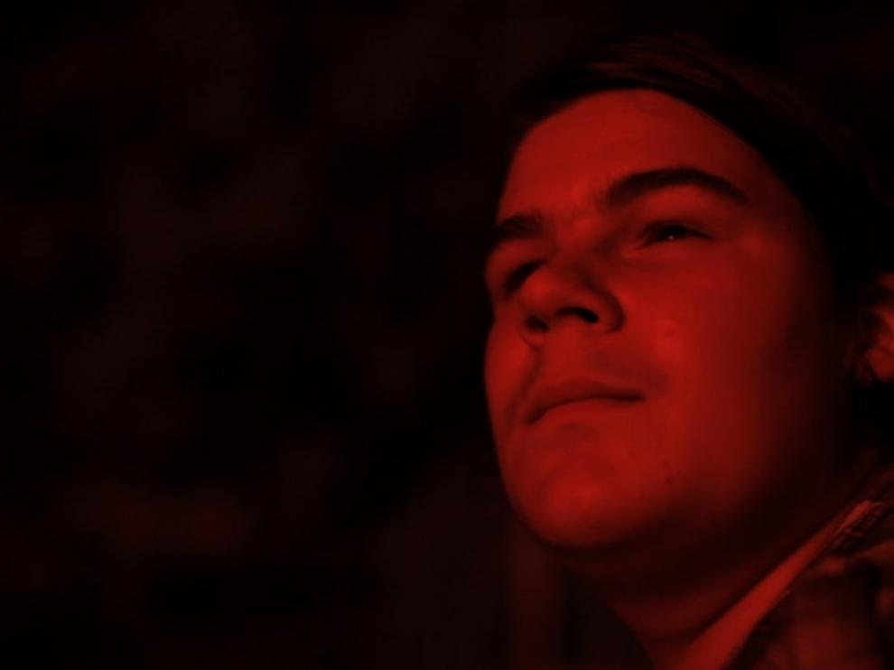 Gros plan du visage d'Armand, éclairé par une lumière rouge