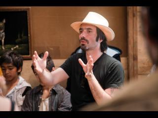 Un homme portant un chapeau de cow-boy parle an faisant des gestes