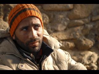 Gros plan du visage d'un homme, adossé contre un mur de pierre