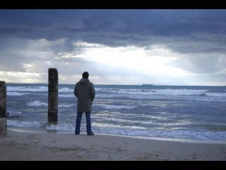 Homme debout devant la mer de loin