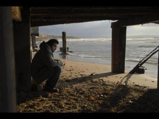 Jeune homme assis sous un ponton, face à la mer