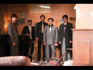 Cinq hommes debout, bouches bées, devant une porte