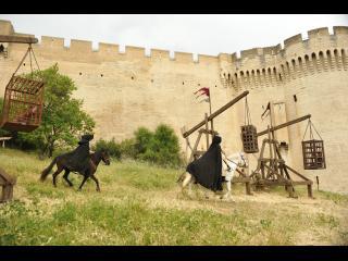 Deux cavaliers vêtus de capes noires s'approchent de l'enceinte d'un château-fort