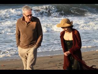 Un homme et une femme marchent au bord de l'eau, sur la plage