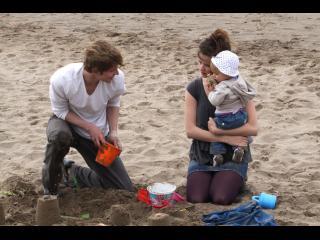 Un jeune homme et une jeune femme portant un bébé font des châteaux de sable sur la plage