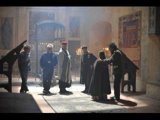 Scène de tournage : le réalisateur place et fait répéter les acteurs, dans une église