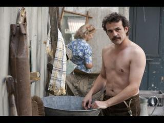Comédien jouant le rôle de Brassens, torse nu, faisant une lessive dans une bassine en cuivre