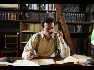 Comédien jouant le rôle de Brassens lisant un livre et fumant la pipe dans une bibliothèque