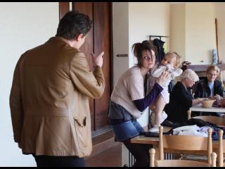 Une jeune femme s'occupe de son bébé tandis qu'un homme lui parle, derrière elle, des personnes lisent, assises à une table