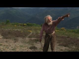 Diourka montre du doigt un point au loin, dans un champ en plein coeur des montagnes