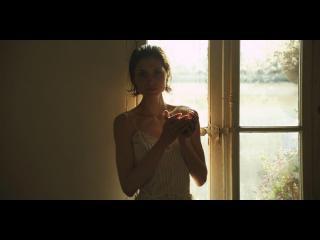 Une jeune femme portant une nuisette blanche est devant une fenêtre, les mains jointes, elle regarde la caméra
