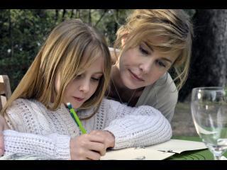 Une femme blonde aide une petite fille blonde à faire ses devoirs, penchée au-dessus de son épaule, assises à une table de jardin