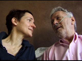 Un homme sous oxygène et une femme aux cheveux courts se regardent amoureusement