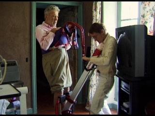 Homme sur un appareil thérapeutique, aidé par sa femme