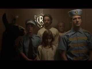 Dans un ascenseur, trois personnes habillées de pyjamas de détenus, un policier et un groom