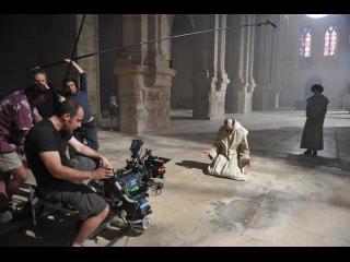 Scène de tournage : la caméra filme un religieux tombé à genoux, les paumes ouvertes vers le ciel