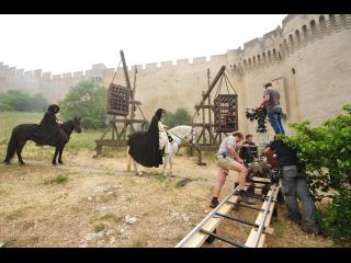 Scène de tournage : la caméra est sur un rail, près du château-fort, des cavaliers habillés en noir s'en approchent