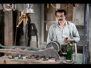 Comédien jouant le rôle de Brassens dans un atelier, la pipe à la main