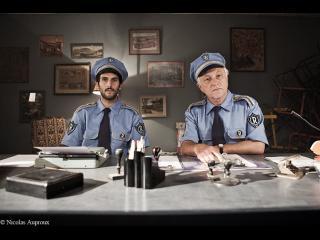 Deux policiers assis derrière un bureau regardent dans la même direction, perplexes