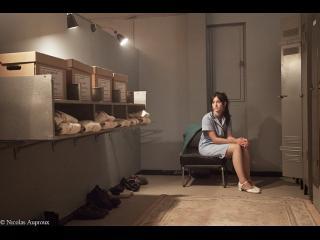 Une femme, en uniforme est assise sur une chaise, devant elle se trouve des boîtes et des uniformes