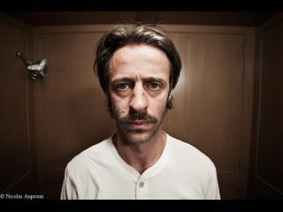 Gros plan sur le visage d'un homme portant une moustache, l'air fatigué