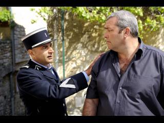 Un gendarme, la main posée sur l'épaule d'un autre un peu costaud