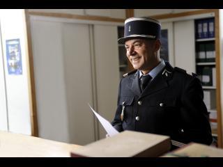 Un gendarme, très souriant, tient une feuille de papier dans la main