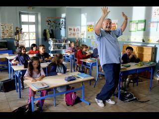 Un homme assez costaud est debout en train de danser, dans une classe remplie de jeunes élèves