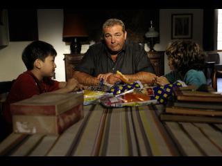Un homme est assis à table avec un jeune garçon