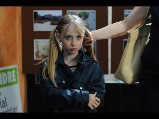Une petite fille blonde avec des couettes fait une moue boudeuse, elle est dans ce qui paraît être une agence immobilière