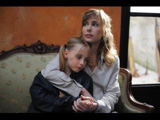 Une femme blonde câline une petite fille blonde, sur un canapé blanc