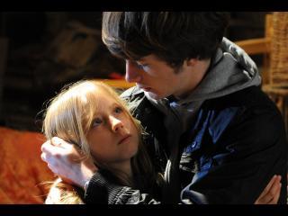 Un jeune homme serre une petite fille blonde dans ses bras, ils se regardent fixement dans les yeux