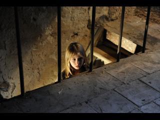 Une petite fille blonde, dans un escalier, guette ce qu'il se passe à l'étage supérieur