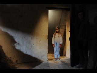 Une petite fille blonde est dans entrebâilleur d'une porte
