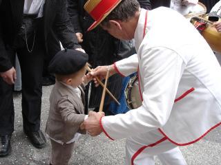 Papé en tenue traditionnelle apprenant le tambourin à un enfant coiffé d'un béret