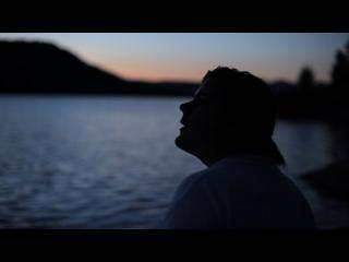 Armand, devant un coucher de soleil au-dessus d'une étendue d'eau