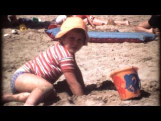 Petit garçon jouant dans le sable avec un seau qui se trouve devant lui