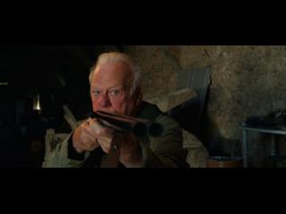 Un homme surveille quelque chose dans le viseur de son fusil, en intérieur