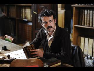 Comédien jouant le rôle de Brassens lisant un livre dans une bibliothèque