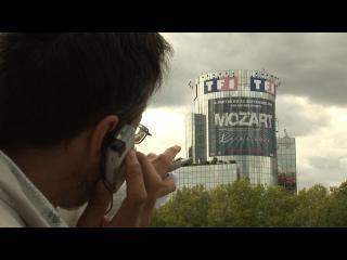 Pierre Carles, de dos, devant le building de TF1 à Paris