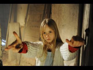 Une petite fille blonde, dans une sorte de couloir, tend les bras vers la caméra