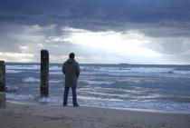 Homme debout face à la mer
