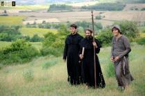 Deux moines et un jeune homme en costume médiéval marchent dans une plaine verdoyante