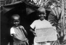 Deux enfants camerounais devant une tente, derrière laquelle se trouve des palmiers