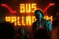 """Groupe de musicien sur scène, derrière eux une inscription au néon """"bus palladium"""""""
