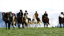 Groupe de cavaliers sur une plaine, au milieu des montagnes
