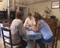 Trois femmes, de trois générations différentes, sont assises autour d'une table et regardent des photos